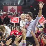 Liberal Leader Justin Trudeau, holding his son Hadrien, makes his way through a crowd of supporters during a rally Sunday, October 4, 2015 in Brampton, Ont. THE CANADIAN PRESS/Paul Chiasson